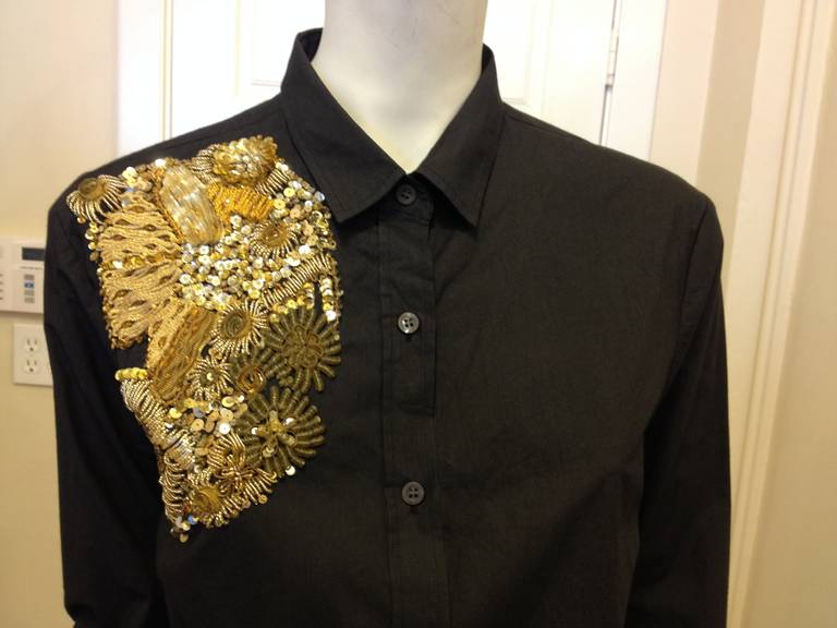 This basic black button down shirt has extraordinary detail and workmanship at the shoulder.  Ideal for making a statement or adding a little glitz and glamor to your everyday look.  Gold sequins, beads and ribbons create a stunning, multi-textured,