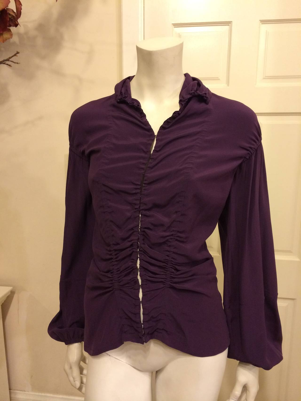 Deep and sumptuous royal purple makes this piece especially beautiful. The loose bell-shaped sleeves are elasticized at the wrist, and the lines of drawstring ruching that run down the front and back add a lovely gathered texture. The front is fixed