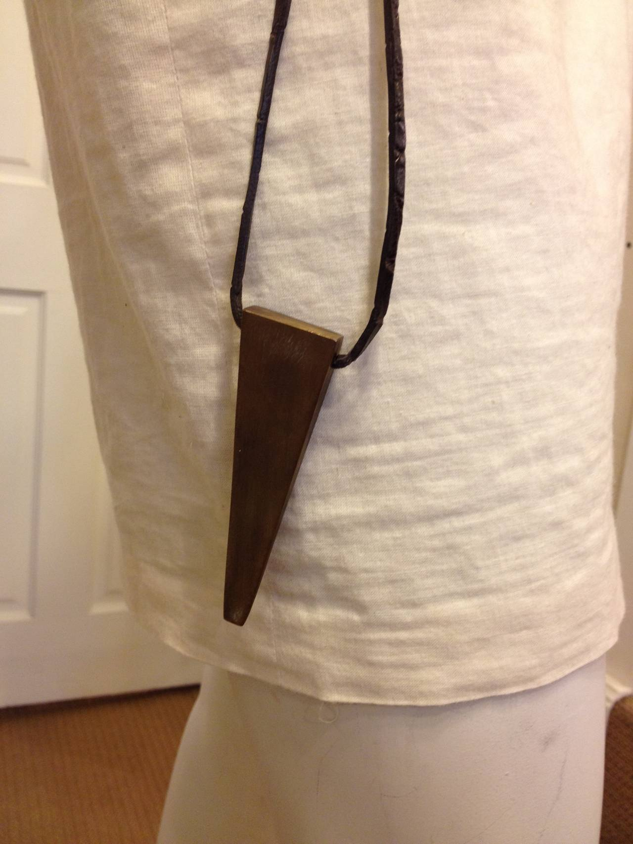 This belt is made of a strip of alligator leather in a deep woody brown color, tapering at either end and finished without hardware for a raw, organic look. A bronze-toned angular sliver of metal hangs from a leather cord on one hip. This piece has
