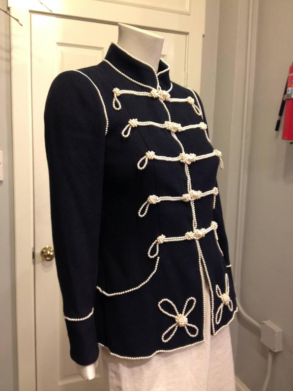 Chanel does Sgt. Pepper! This piece is an absolute show-stopper - the deep navy woven material is cut sharp with a high collar and nipped-in waist, and trimmed with a plethora of iconic Chanel pearl strands that style the piece like a marching band