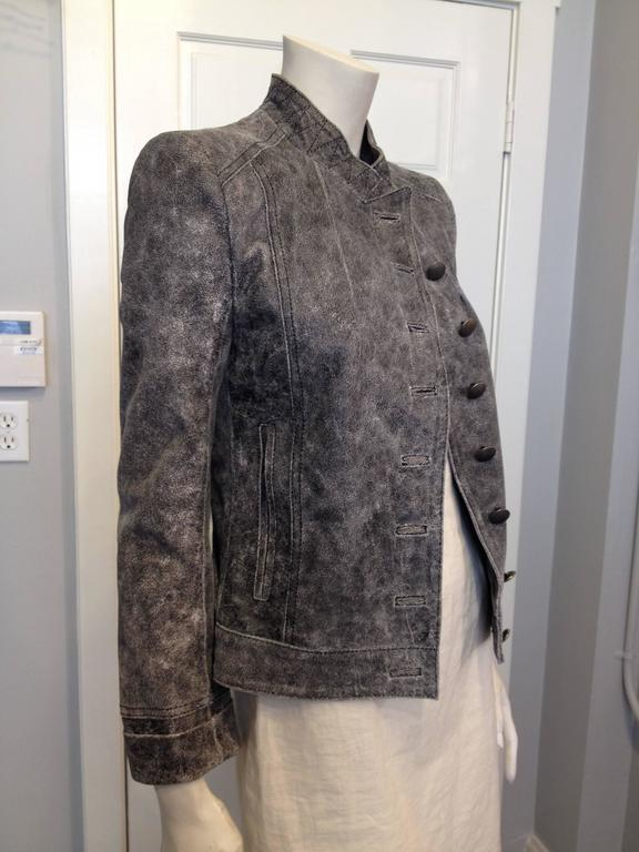 Beautiful and simultaneously angular, hard-lined, and edgy, this leather jacket is purely Ann Demeulemeester. It is cut super sharp, with an asymmetrical closure at the front studded with a row of matte embossed metal buttons. The collar is high and