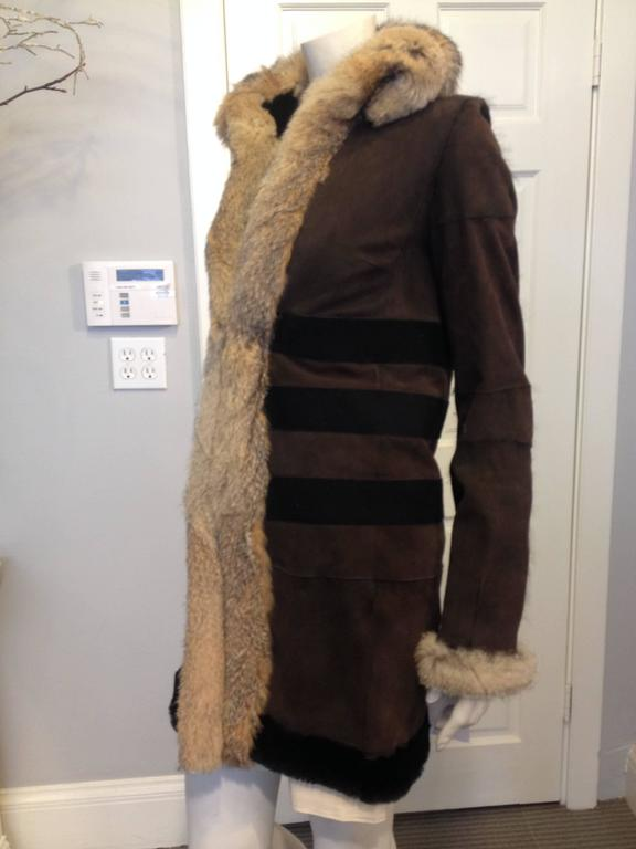 You'll always be cozy and warm in this Balenciaga coat. Greyish tan fur trims the cuffs and collar, while a super soft black zorro fur lines the entire interior of the coat. The luxurious brown suede exterior is perfect for any cold city, while the