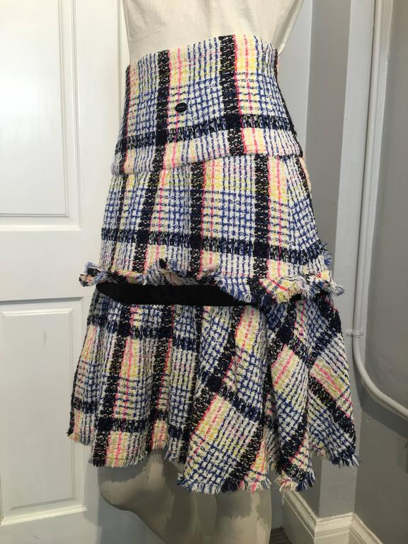 High waisted flared skirt, in white, blue, yellow, pink and black plaid tweed, with a 10.5 inch long ruffled tier, accentuated by a 1.5 inch thick black satin band. This piece is from the 2009 Spring collection.