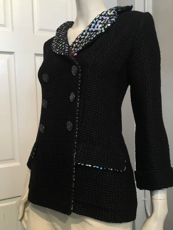 Chanel black double breasted jacket in a big weave fabric in alternating glossy and muted threads. Silver color reflective scales cover the lapels, the inside flaps of the two front pockets and the inside of the cuffs. The six buttons are dark