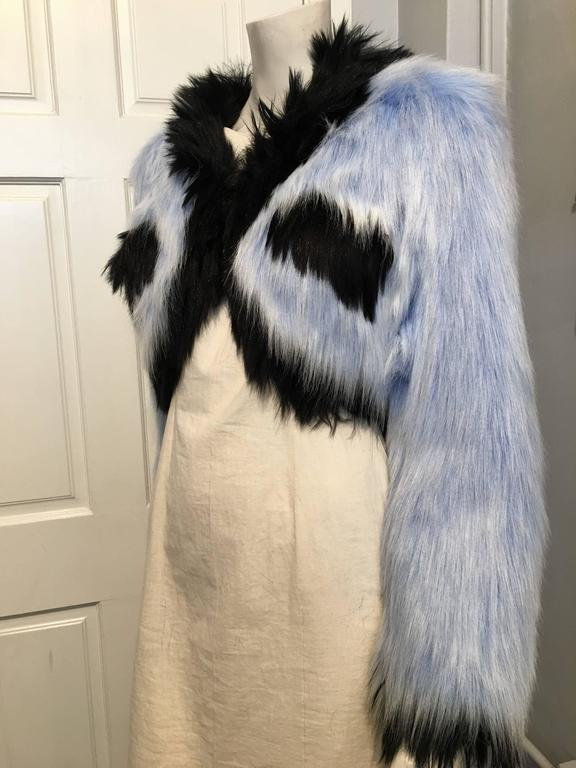 Chanel faux fur cropped jacket in blue and black. it closes with a single hook and eye. The black silk lining features the brand name in large white text.