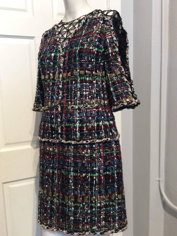 Chanel ribbon dress with black lace/net accent on sleeves, shoulders and neckline.  Braided horizontal accent on lower hips; multi-colored ribbons in black, green, teal, wine, red and silver; 1/2 sleeves, low cut v-neck with lace/net inset, jeweled