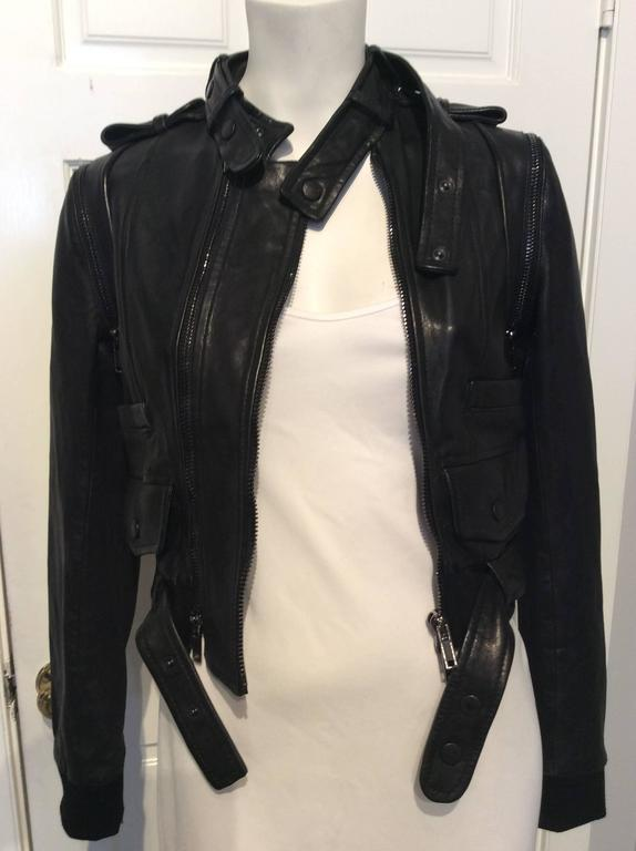 This black lamb leather Givenchy moto jacket is both iconic and stylish.  The cropped jacket has an off-center zipper with an additional venting zipper to balance, removable collar strap, belt and sleeves.  Ribbed waistband and cuffs complete the