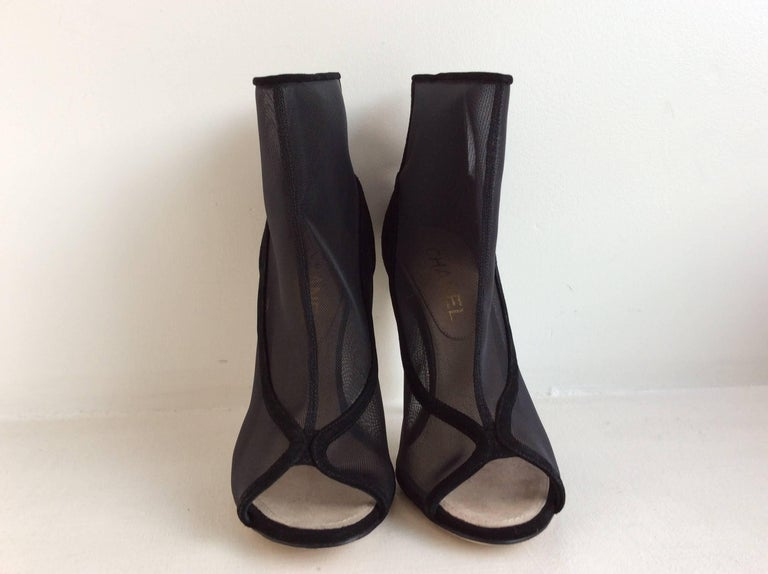 Chanel black nylon mesh and suede open toe booties in size 39 (8.5 USA). The clear acrylic heel is 4.5 inches. The booties back is in black suede with two small gold toned CC on each of the outer upper part. For easy wear they have a 4 inches zipper