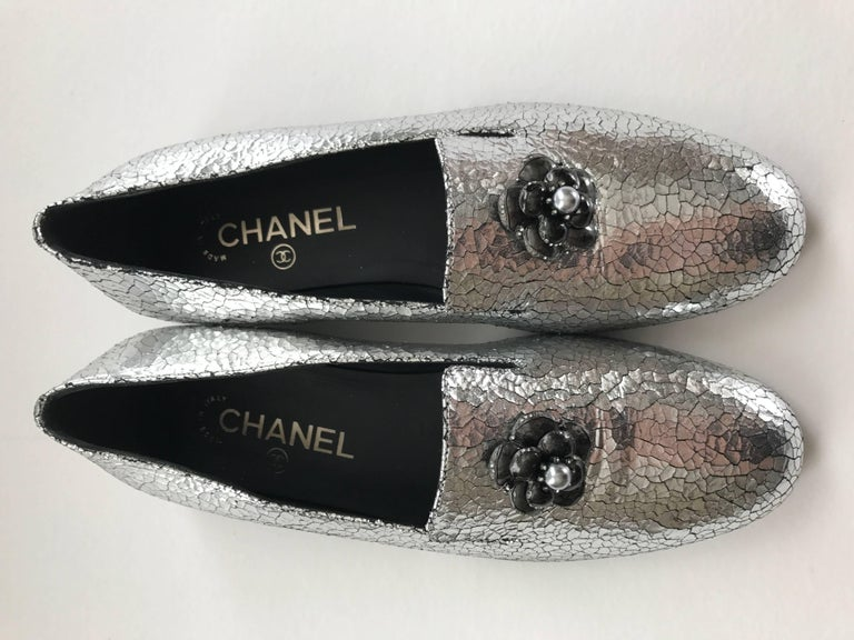 Eye-catching Chanel silver loafers in crackled leather with Gripoix pewter camellia embellishment. The flower has  tiny rhinestone edging and a grey silver pearl in center. The marked size is 37 1/2 or US 7 1/2.