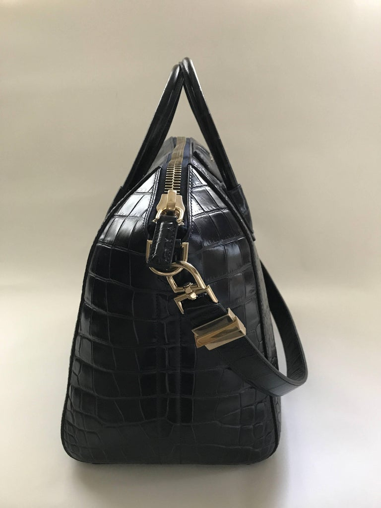 Givenchy large midnight blue Antigona bag in mock croc calf leather. Muted gold hardware, two top handles and a 29in x 1in shoulder strap. Black fabric lining with three wall pockets including a larger one with zipper. Dimensions: H 12.5in / W 18in