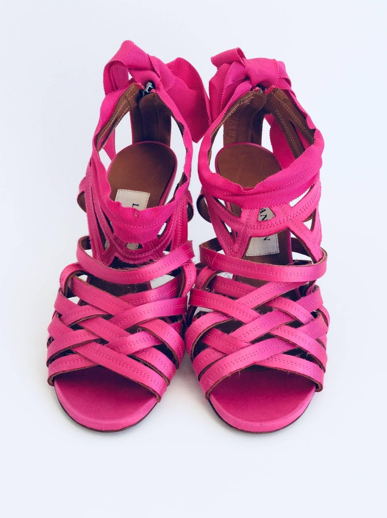 Lanvin candy pink sandals made with unfinished strips of satin a  gros grain ribbon that closes in a bow at the ankle. The height of the pewter metallic heel is 4in and they have a zipper in the back of 2 3/4in.   Please note the shoes are sold as