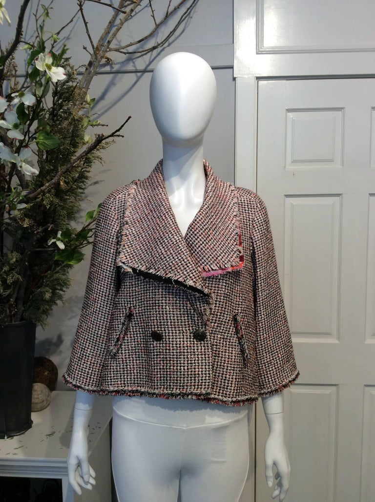 Chanel bright pink, white, and black tweed A-line double-breasted jacket with silk and tweed fringe throughout. Dual pockets with fringe accents. Cropped fringe sleeves. One black button closure at interior. Two gold and black buttons at front.