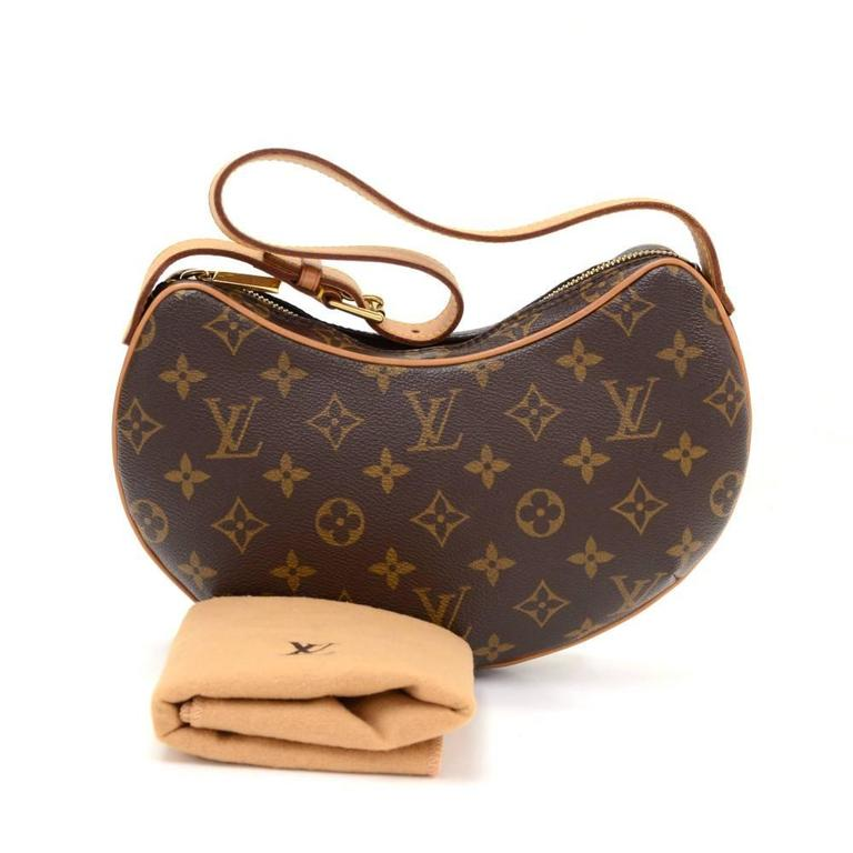 Louis Vuitton Pochette Croissant in monogram canvas. Top is secured with a zipper. Inside has red alkantra lining and 1 open pocket. Carried on one shoulder or in hand with adjustable cowhide leather strap.