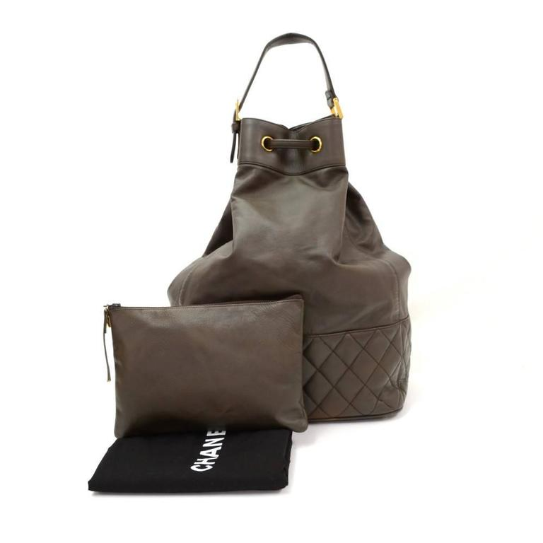 Chanel bucket shoulder bag in dark brown leather. It has stitched around the bottom. Main access has leather string closures. Inside has black leather lining with attached small pouch. Can be used as backpack, shoulder or hand bag.  Made in:
