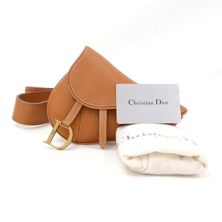 Christian Dior saddle bag in brown leather. Main access is secured with flap and stud closure. Comfortably worn around waist.Belt size: 85 stamped. Adjustable app from 29.5 - 32.9 inches or 75 - 83.5 cm