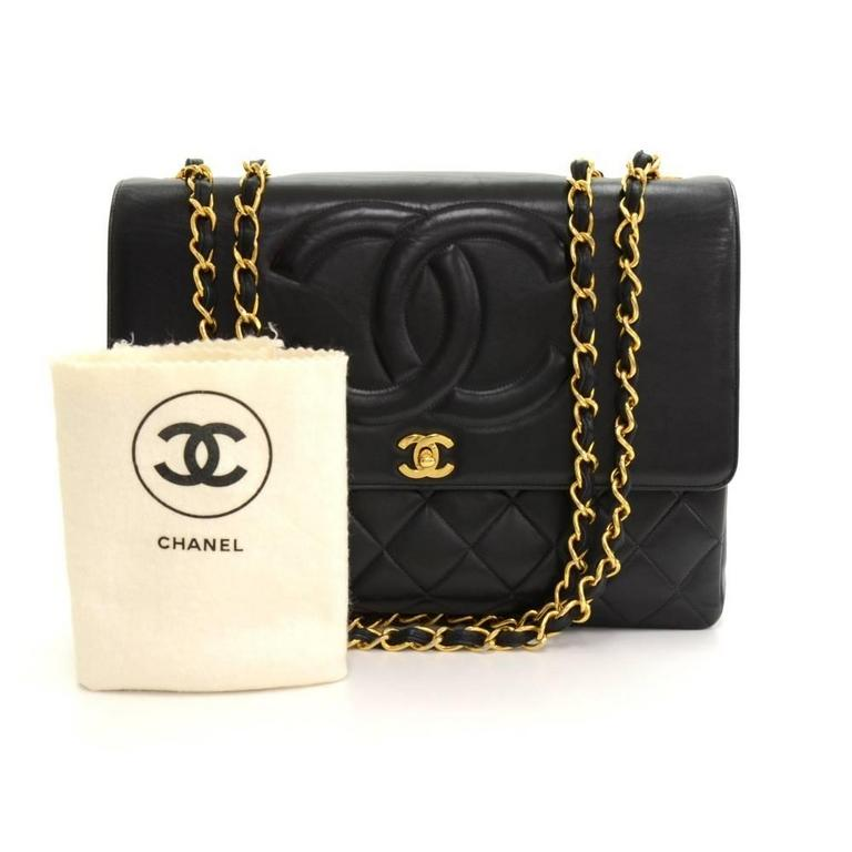 Chanel Maxi Jumbo in black quilted leather. It has flap top with famous large stitched CC on the flap. Outside on the back has 1 open side pocket. Inside has Chanel red leather lining and 2 pockets: 1 zipper and one open. Comfortably carried on