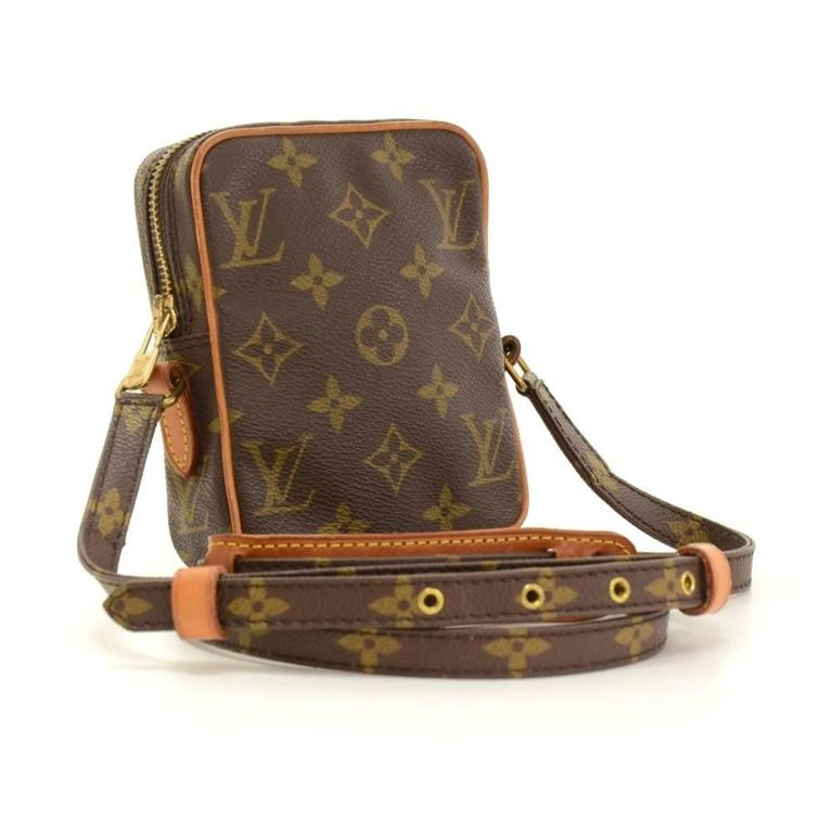 Louis Vuitton Mini Danuebe shoulder pochette/bag in monogram canvas. Top is zipper closure. Inside is in brown lining with 1 open space. Can carry on shoulder or across body with adjustable strap. Very practical item.  Made in: France Serial Number: