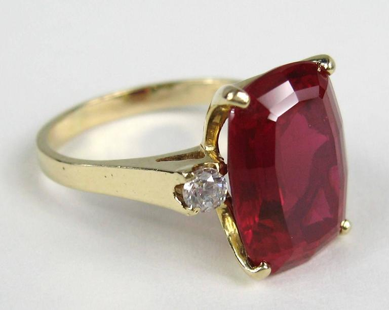 Stunning large center synthetic Ruby gem with two diamonds flanking each side of the stone. 