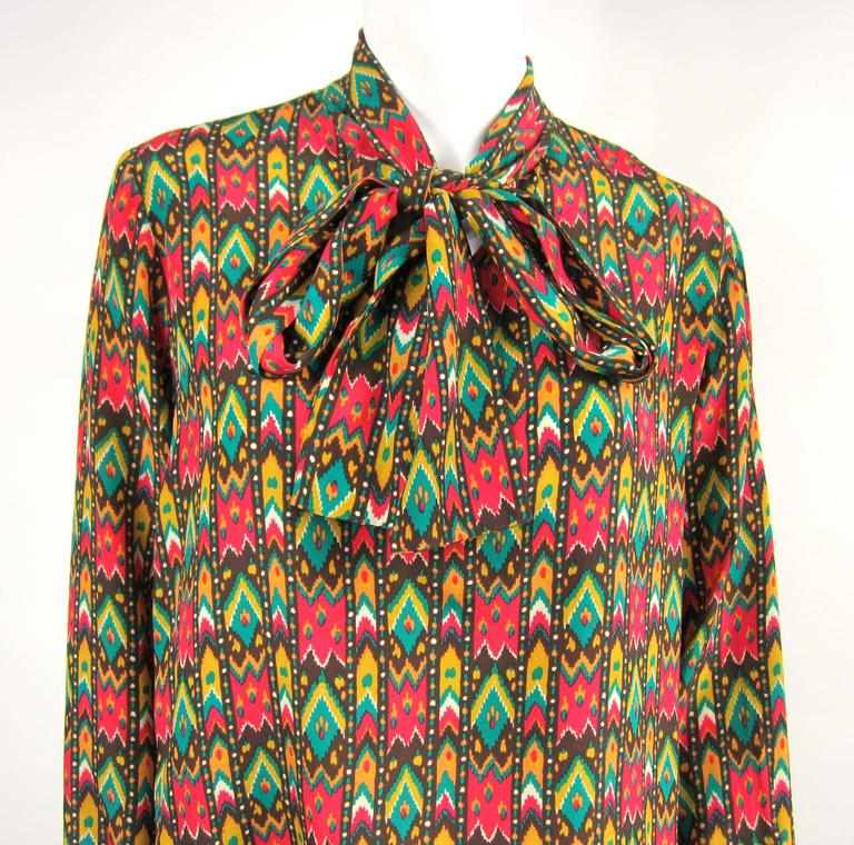 Has a bit of a southwestern vibe! YSL silk 1970s Blouse  Measuring  Up to 40 Bust  Up to 40 waist  25 long  23.5 sleeve, buttoned cuff  Any questions please call, email or hit request more information