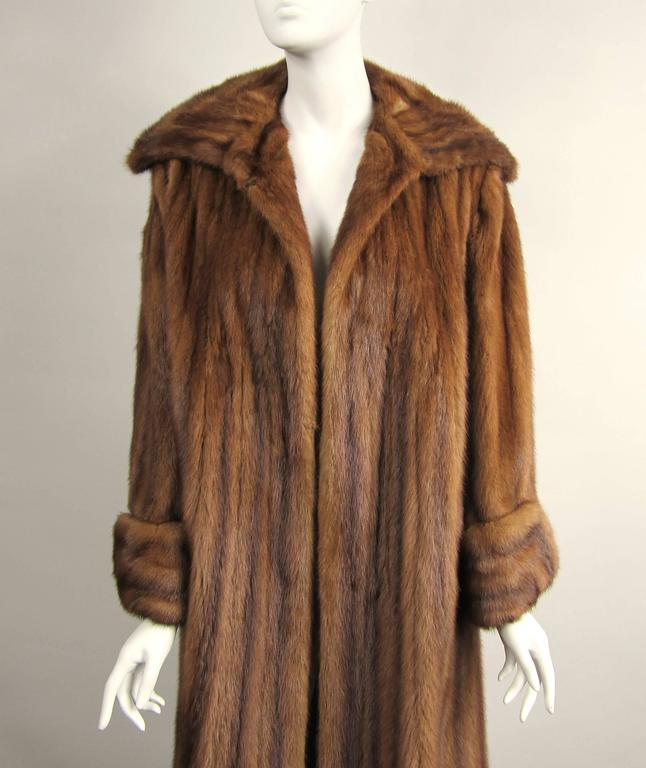 This is spectacular, Brown soft and supple swing Mink Coat  The cuffs on this coat are stunning  Mink is in amazing condition  This will fit a wide range of sizes from a 10-16  It has one eye hook at the neck which can be moved to fit larger or