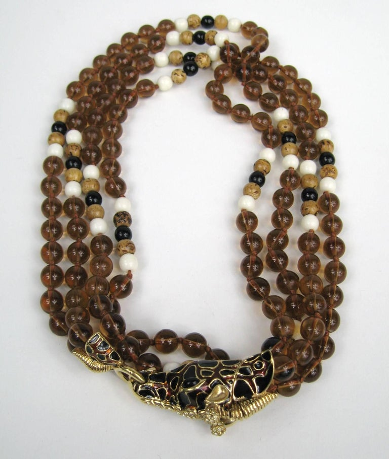 New, never worn  giraffe double strand Ciner Necklace Amber colored, wood and black beading with Black and brown enamel work. Measures 42 inches end to end. It is doubled on the display.  Matching Clip on earrings listed as well. Visit our store