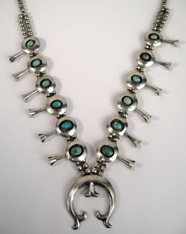 Another stunning Navajo Squash blossom Sterling silver necklace. Shadow box set turquoise stones totaling 12. Naja at the bottom measuring 2.23 inches x 2.15 inches - Blossoms are 1.79 inches long on Double beaded chain that graduates to a single