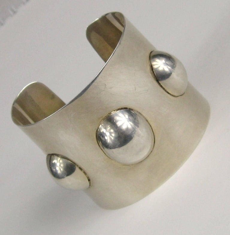 Stunning Sterling Silver Mexican Cuff  with a Sleek design with surrounding ovals. Measuring 2.06 inches wide or 52.49mm it will fit a 6.5 up to an 8 as sterling is pliable. The Bracelet is hallmarked insidefrom a shop in Mexico called Perlita. This