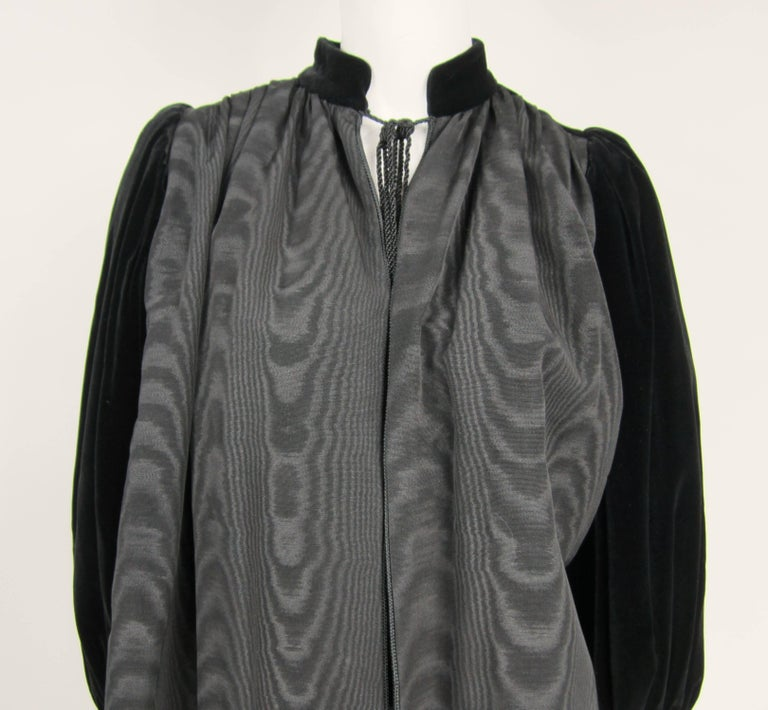 This is a stunning Yves Saint Laurent YSL black on black Velvet sleeved Jacket. Mandarin Collar with tassel cord closure. Balloon sleeves.. Banded cuff 2 slit hidden pockets. Labeled a Size 34 Measuring approximate up to a 42 chest -- Open waist --