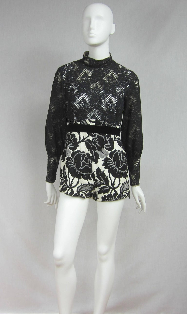Vintage Mignon One Piece Hot Pant with matching wrap maxi skirt. Large Black Floral Motif on a white background. Crochet Top Illusion lined at the shoulders, white backed from the Bust down. Poet Buttoned Sleeves. Wide Velvet Belt on both pieces.