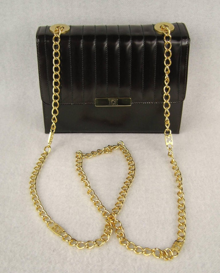 Kelly Brown Leather Ribbed Leather hand bag. Tags still in hand bag along with dust cover. Gold Tone link chain as shoulder strap. Zippered inside compartment. Gold Leather lining. Measures - 8 in. x 6 in.  x 3 in. deep - 24 in.  long chain strap.