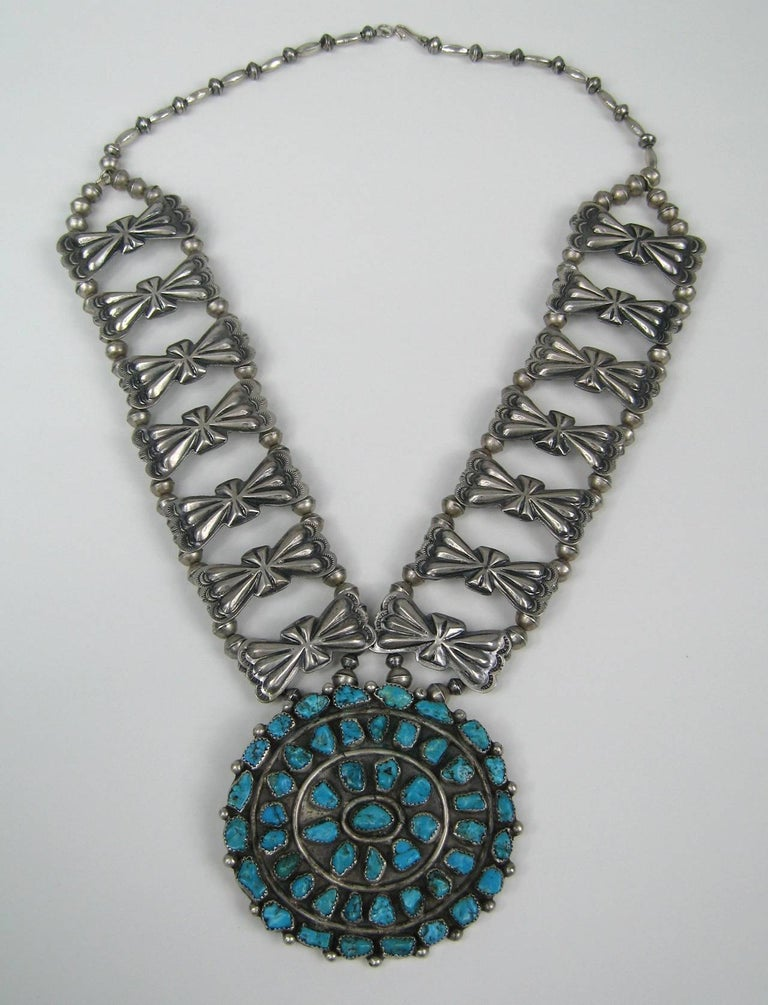 Massive handmade Turquoise hanging from a butterfly motif necklace. The craftsmanship on this is stunning. The oval has a pin back on it. The oval drop measures 3.22 in wide  x 3.09 in high. The links are 1.77 in x .78 in set on a double beaded