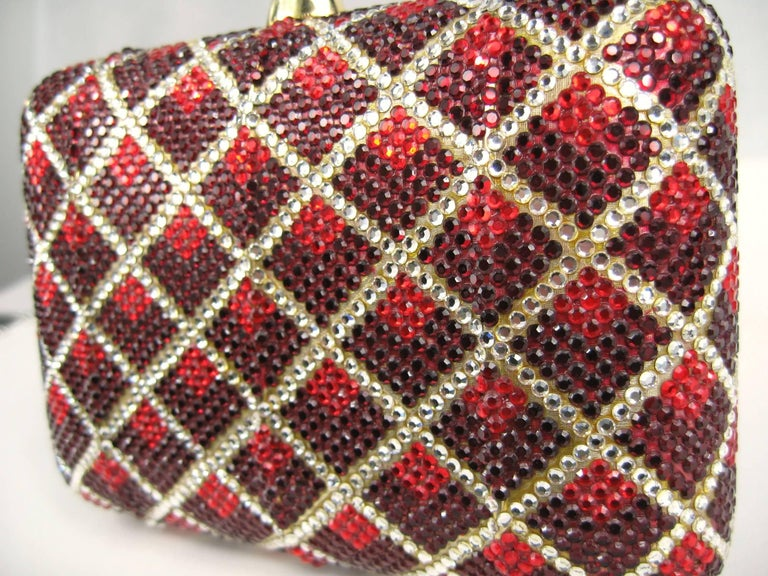 Stunning Clear and Red Swarovski Crystal on this magnificent Judith Leiber Clutch. A must-have for the upcoming holiday season, as well as any black tie event. Runway ready! Gold leather interior that holds an attached chain shoulder strap