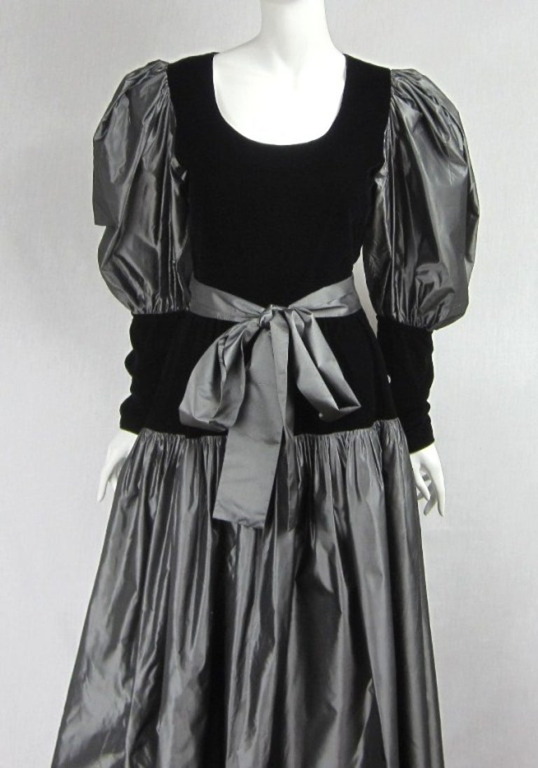 Gray and black, stunning combo in person. Large oversized balloon sleeves. Buttoned cuffs. Fitted waist dropping into a pleated silk skirt. Will fit a 8 nicely. Please be sure to check our storefront for more fashion as we have both Vintage and