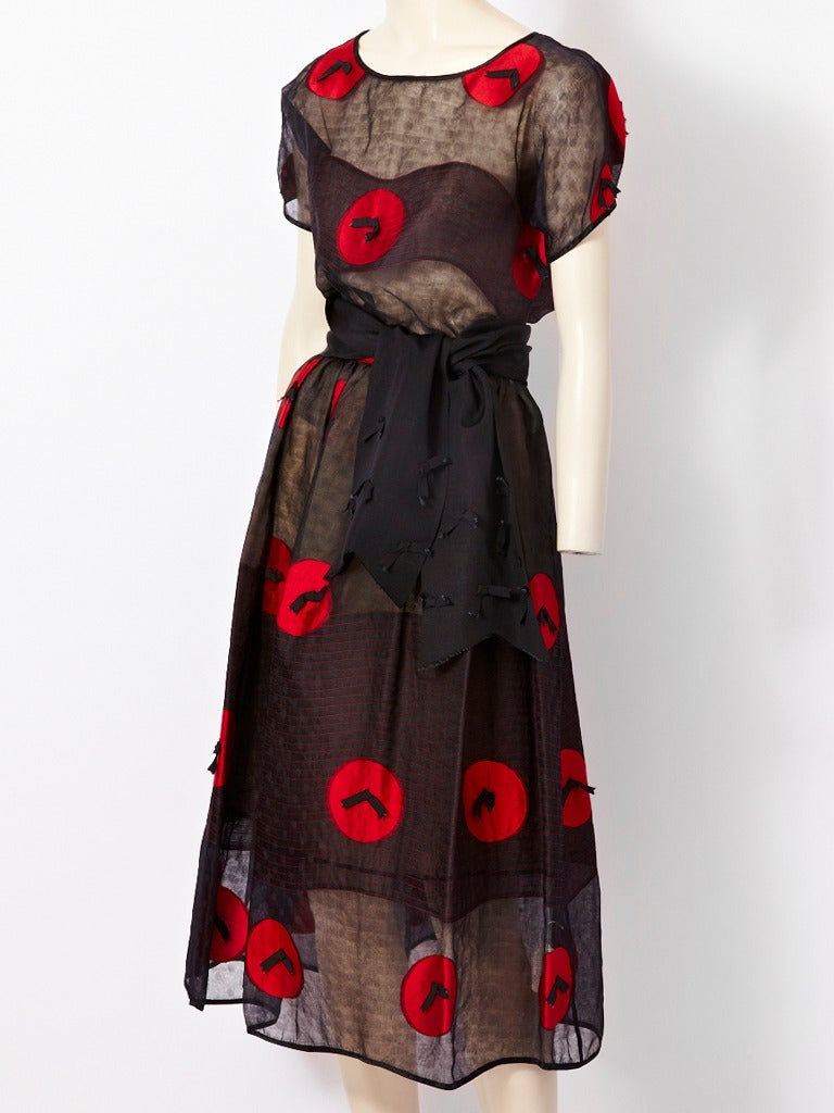 """Geoffrey Beene, sheer, black, dotted organza top and skirt ensemble with wide gross grain sash. Fabric has a pattern of woven red circles with appliqued gross grain bows in the center of each circle. Red """"wave"""" pattern top stitching further"""