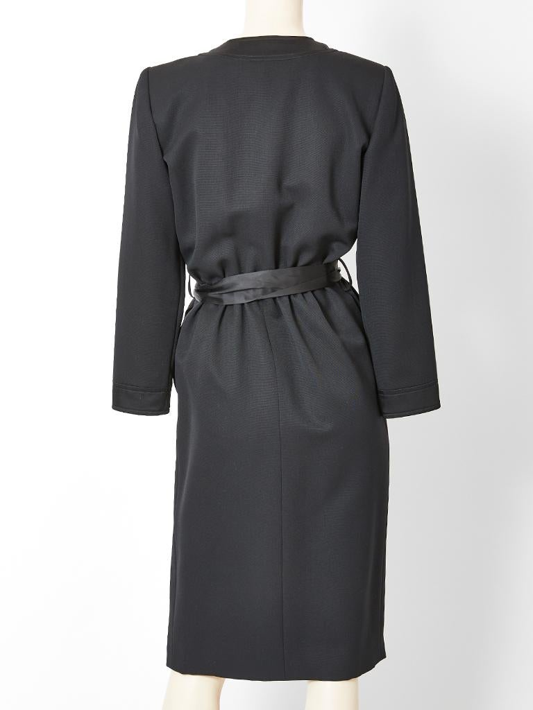 Yves Saint Laurent, Rive Gauche, black faille cocktail dress, having satin edging detail and a black satin bow at the waist. Dress has side button closures embellished with round, black enamel and rhinestone buttons.