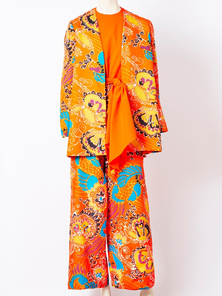 Beene Boutique, orange, poly crepe,  jumpsuit with a wide leg pant, in a colorful print with an orange ground. Top is sleeveless with a jeweled neckline. Attached sash, criss crosses in the back and ties in the front. There is a matching, printed,