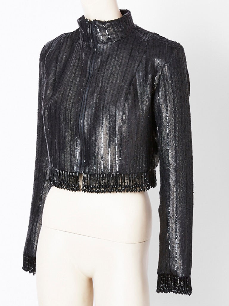 Fernando Sanchez,  fitted, sequined and beaded cropped evening jacket. Jacket has a mixture of matte and shiny sequins. It has a zipper closure with a high neck. It is cropped to just above the waist with 2 inches of fringed jet beading all along