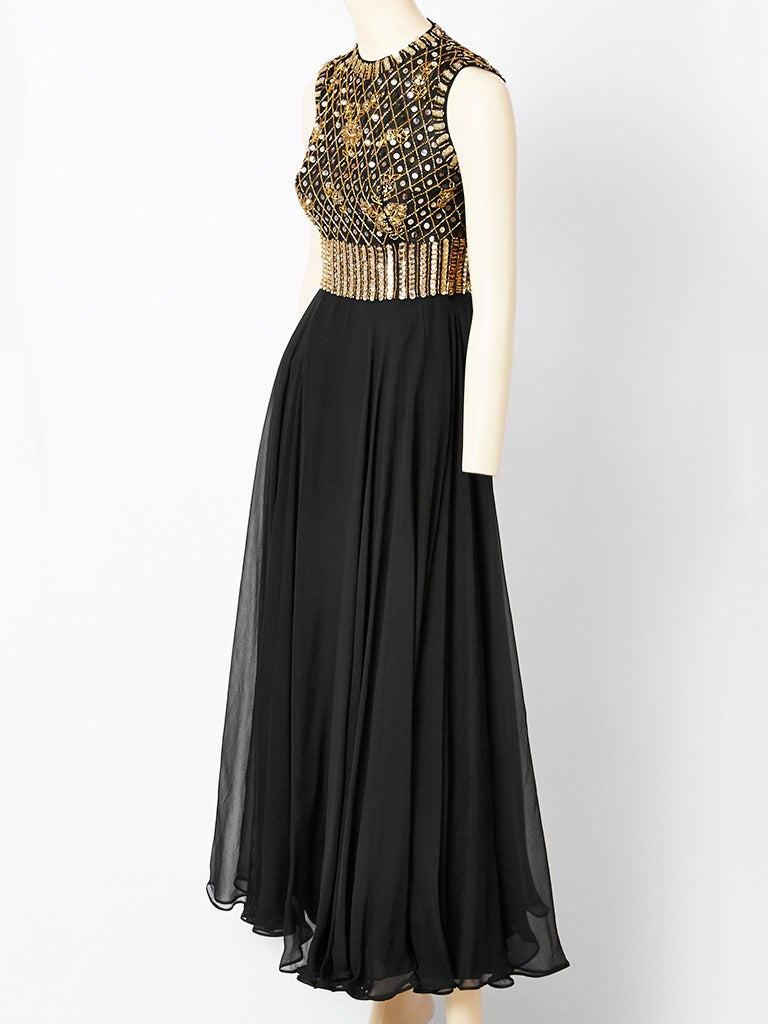 Evening gown, having a sleevless bodice encrusted with gold sequins and beads  on black chiffon. Neckline is round. Bodice is slightly empire with a full skirt of layers of black chiffon. Dress was designed for the Elizabeth Arden boutique in the