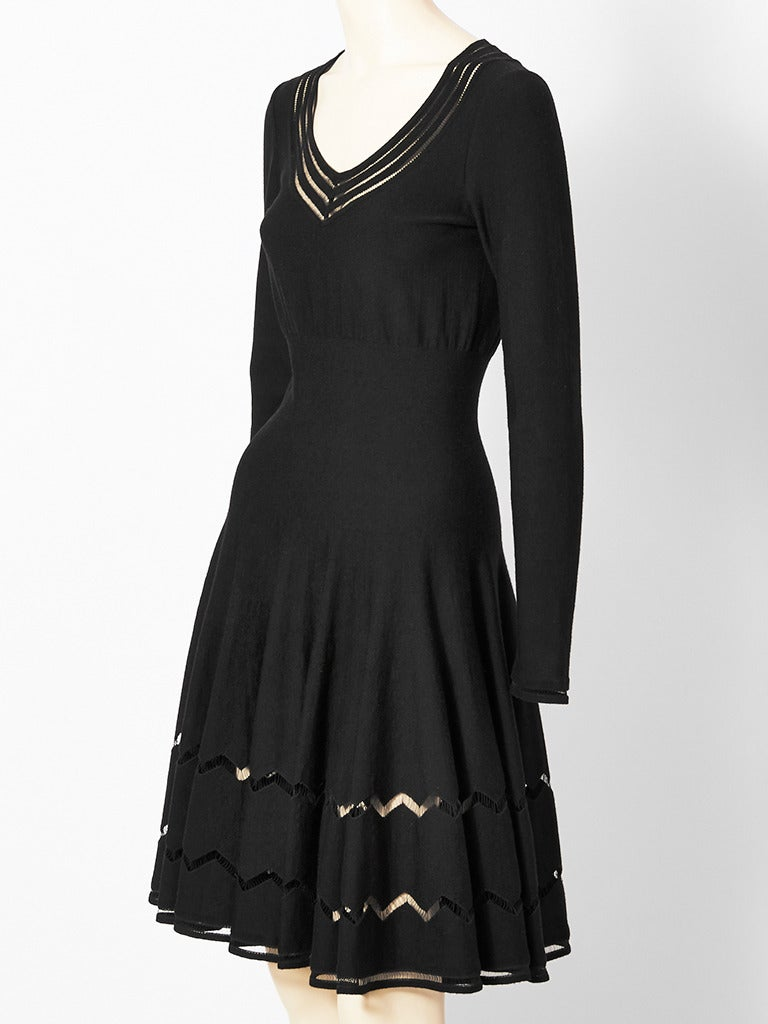 Azzedine Alaia, black wool knit dress , having a scooped V neckline, fitted waist and a full flared skirt. Open work zig - zag pattern detail at the skirt edge, neckline, and sleeve edge.