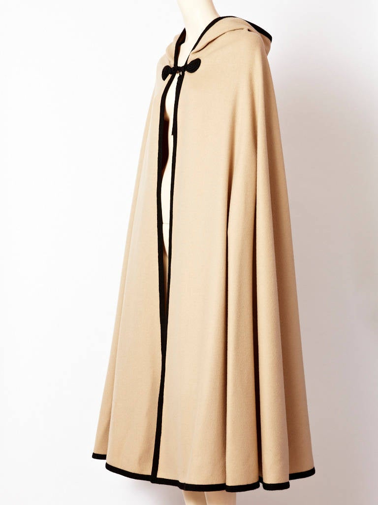 Yves Saint Laurent, pale taupe, wool, Moroccan inspired hooded cape. Cape is trimmed in a wide black braid with passementerie closures and a large tassel. Hood has a large black tassel at  its point as well. C. 1970's.