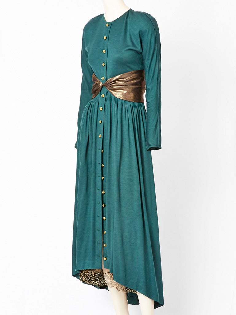 Geoffrey Beene, forest green, jersey dress having an asymmetric hemline , (higher in the front, lower in the back). Buttons down the front w/ knotted lame buttons. Details include a bronze lame cummerbund and petticoat that is edged in bronze lace