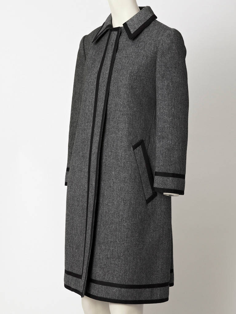 Geoffrey Beene, heathered, charcoal grey, wool coat dress, with pointed collar, and slanted side pockets . Dress has wool braid trim detail.