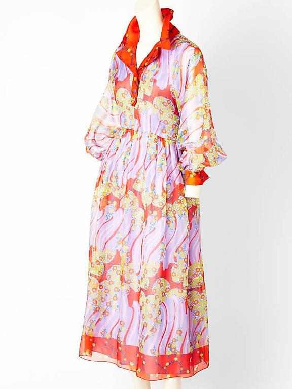 Oscar de la Renta, maxi dress in a silk organza, abstract print in pretty shades of tangerine, periwinkle blue and yellow. Bodice of the dress is shirt style with full sleeves that cuff at the wrist. Skirt is gathered. Late 60's early 70's.