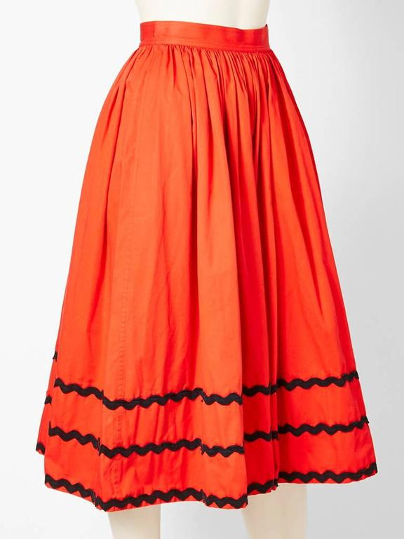 Yves Saint Laurent, Rive Gauche,  orangey-red,  cotton, gathered skirt with black ric rac trim detail at the hem. C. 1970's Deep hidden pockets by the hips.