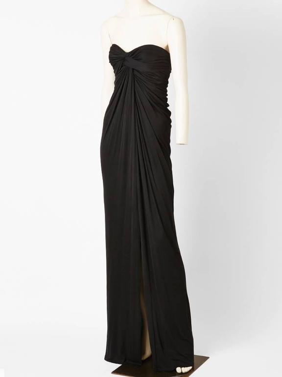 Stavropoulos, black matte, jersey, strapless, Grecian inspired gown, having draping detail from the middle bust to the hem. Dress has a built in corset.