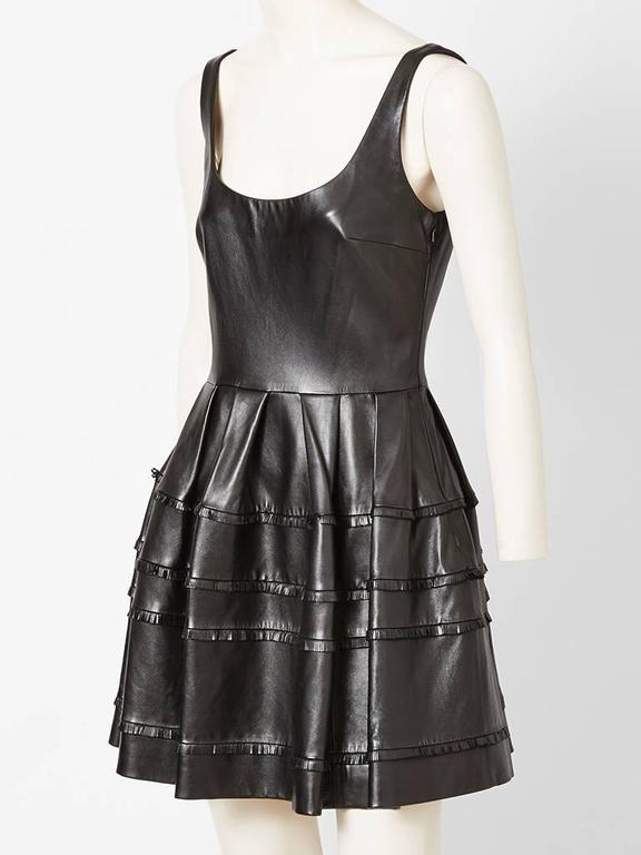 Christian Dior black leather, scoop neck, sleeveless, fitted bodice, dress with gathered skirt, having horizontal fringe detail.