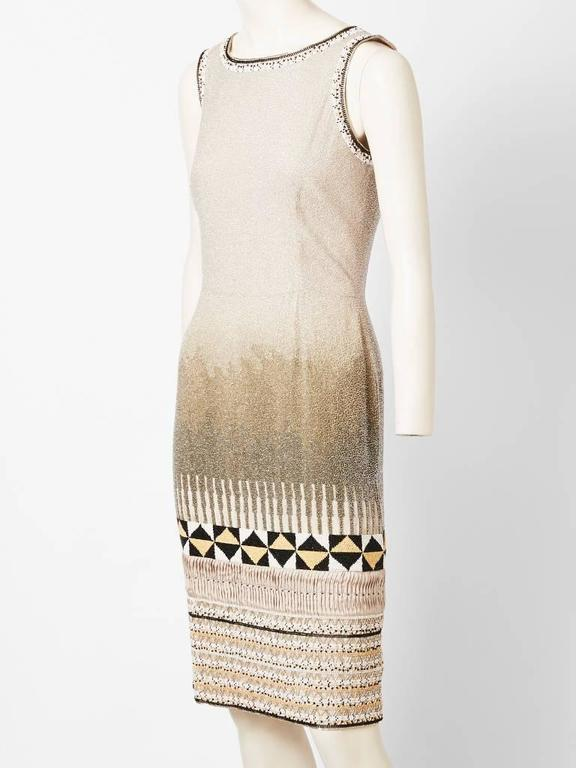 Oscar de la Renta, sleeveless, fitted, cocktail dress encrusted with crystal bead work. Bead work detail includes an ombre pattern at the thighs and African inspired motifs at the hem.