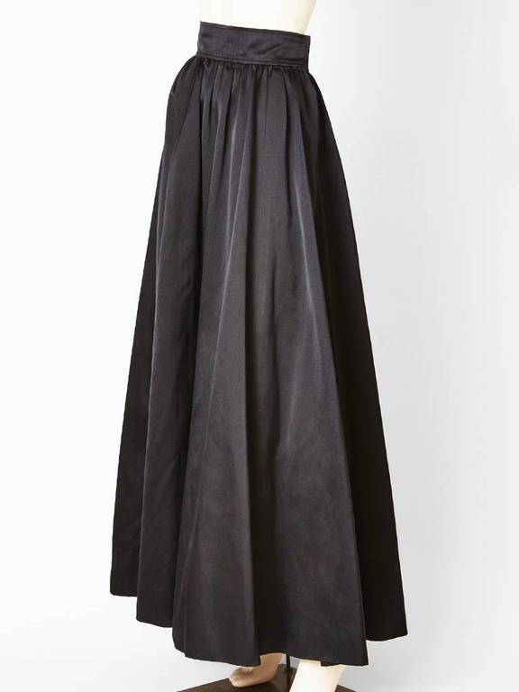 Yves Saint Laurent, black satin, long evening skirt, made of bias cut panels for fullness but without bulk at the waist. Slight gathering at the waistline with a 