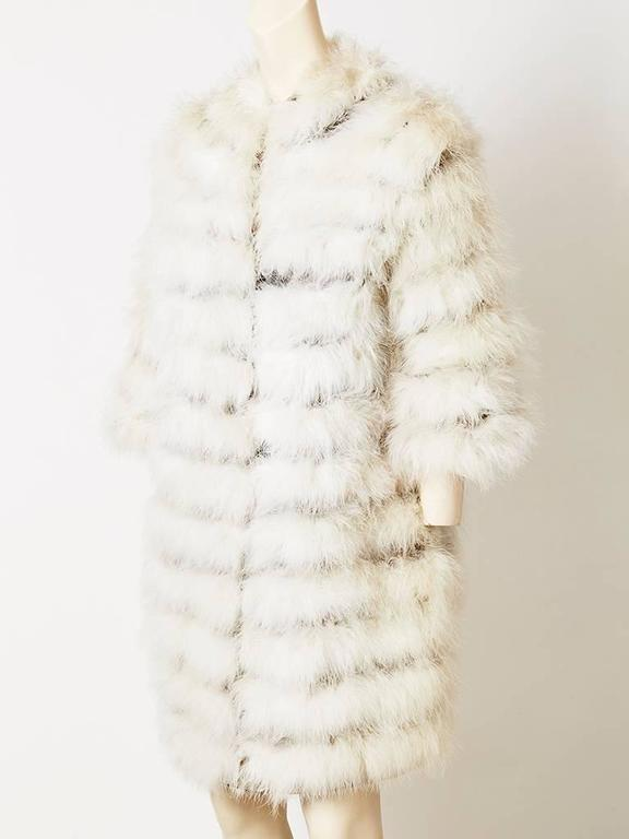 Ivory, maribou feathered, collarless, cardigan/coat with looped button closures. Made of horizontal strips off feathers appliqued on to a grey satin backing.
