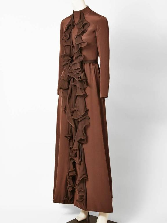 Ronald Amey, silk crepe, chocolate brown, long sleeve, gown with jeweled neckline, having vertical, chiffon, ruffle detail going down the center front.